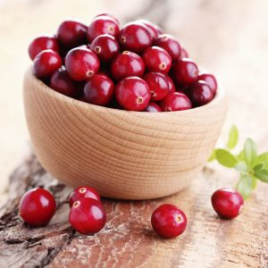 A wooden bowl filled with red cranberries sits on a table, with some cranberries spilling over.
