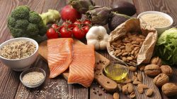 Healthy food like salmon and nuts spread out on a wooden table.