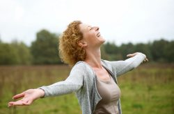 Woman in green field smiling looking up to the sky with outstretched arms.