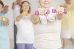 Older women in an exercise class do arm lifts with light free-weights