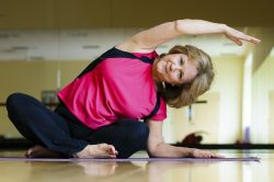 An older woman stretches in a yoga position inside a studio.