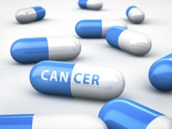 Blue and white pills with Cancer written on the center one.