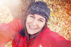 Smiling woman taking a self-portrait in the fall next to a tree.