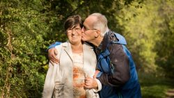 An older couple stands in the sun in front of a treed background as the man kisses his wife on the cheek.