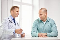 A male doctor talks to a male patient.