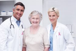 Two doctors flank a patient; all three are smiling.