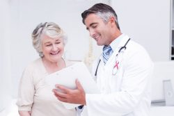 A doctor shows an elderly woman patient good news about her test results.
