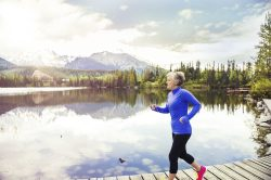 A woman jogs outside next to a lake.