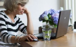 A middle-aged woman sits at a table looking at a laptop computer with a glass of water nearby.