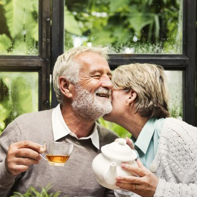 An older couple sit at a table drinking tea as the woman leans over to give the man a kiss on the cheek.