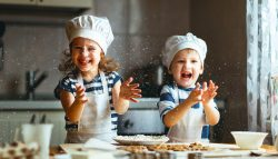 Two young children with chef's hats play while baking in the kitchen with big smiles.