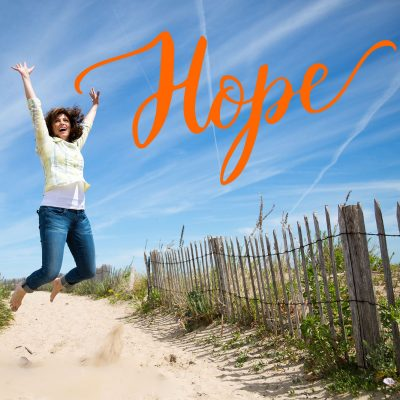 A woman jumps for joy on a beach and the word Hope is in orange in the right hand corner.