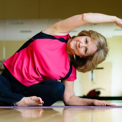 An older woman in a pink shirt does yoga.