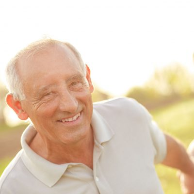 An older man smiles outside in the sun.