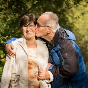 An older couple stand outside and the man kisses the woman on the cheek.