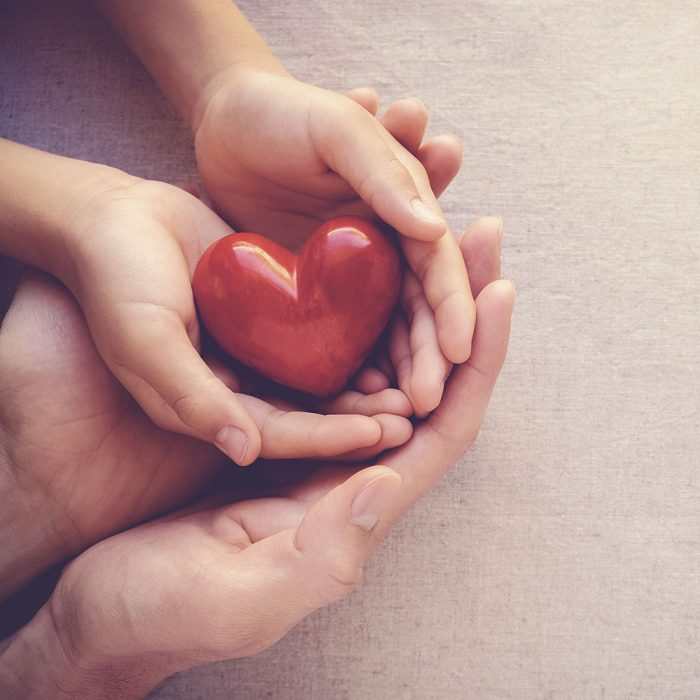 A red wooden heart is held by two sets of hands.