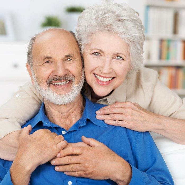An elderly couple smile for the camera.