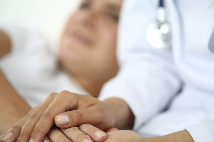 A doctor holds a patient's hands.