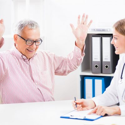A smiling man raises his arms joyfully while across from his smiling doctor in an office.