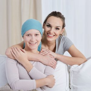 Two women smile for a photo, one has cancer and a scarf around her head.