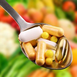 A spoonful of supplement capsules in the foreground with healthy food in the background.
