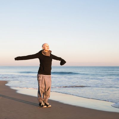 A woman with cancer stands by the seaside on the beach with arms outstretched.