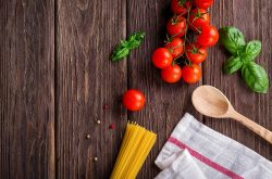 Tomatoes and raw pasta shot from above on a wooden surface.