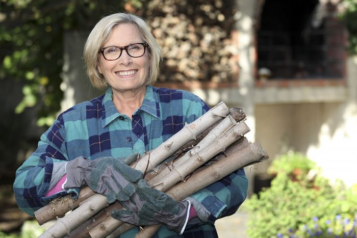 A woman smiles standing outside holding a pile of logs.