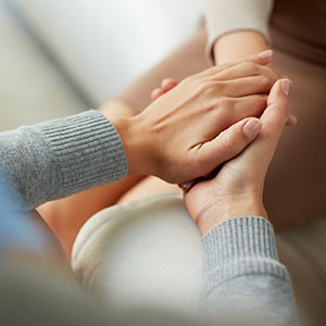 Close-up of two sets of hands clasping one another.