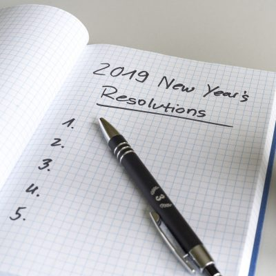 A notepad with a list of new year's resolutions for 2019 written with blank spaces.