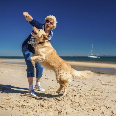 An older woman plays catch with her dog on the beach with joy.