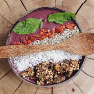 A healthy acai breakfast bowl sits atop a wooden table with a wooden spoon across.
